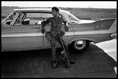 Een soldaat van het Zuid-Vietnamese lege, in 1973, leunt tegen een Amerikaanse auto.