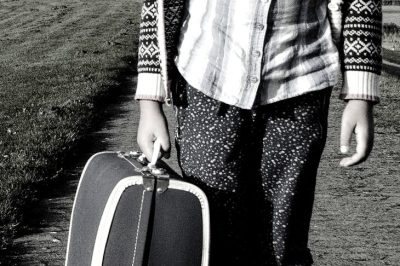 Photo in black and white of a person from the stomach down to the knees. They carry a suitcase in their right hand.